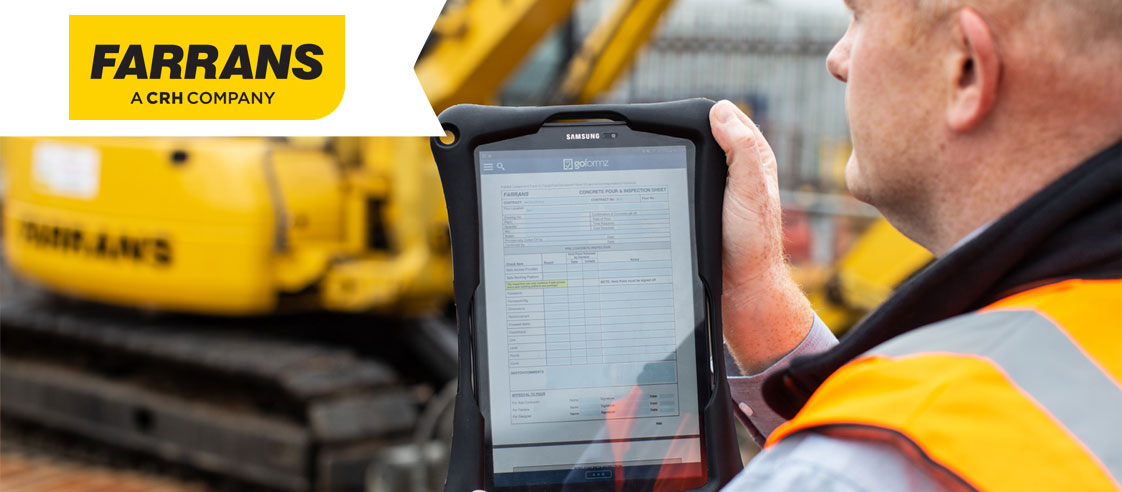 Farrans Construction employee holds tablet with the GoFormz app displayed on the screen while wearing a safety vest, Farrans logo in upper-left corner