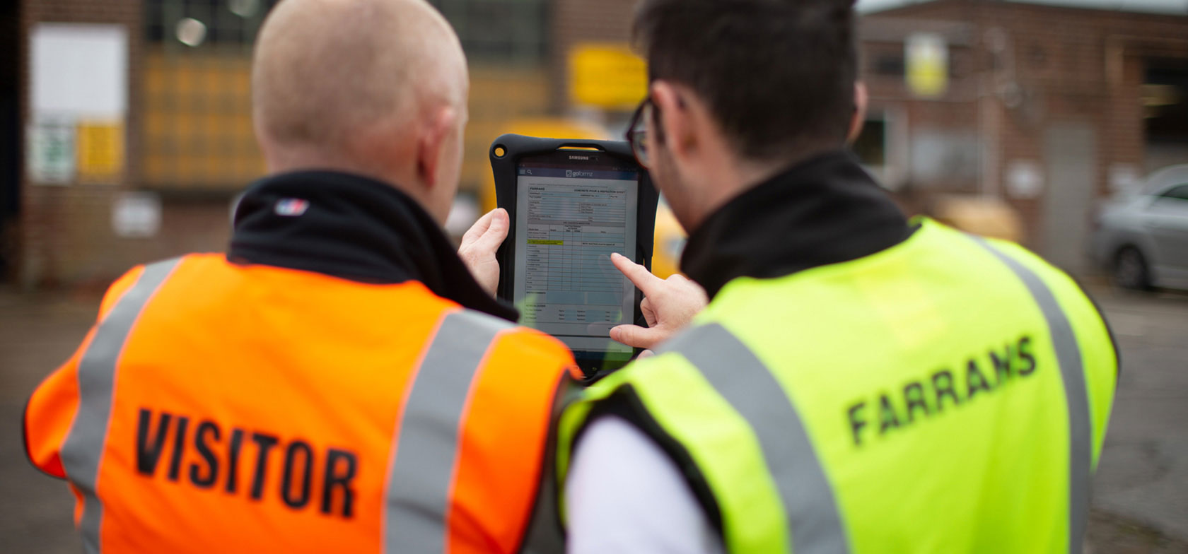 Two Farrans Construction engineers fill out a mobile form in the GoFormz app on a tablet, wearing yellow and orange safety vests