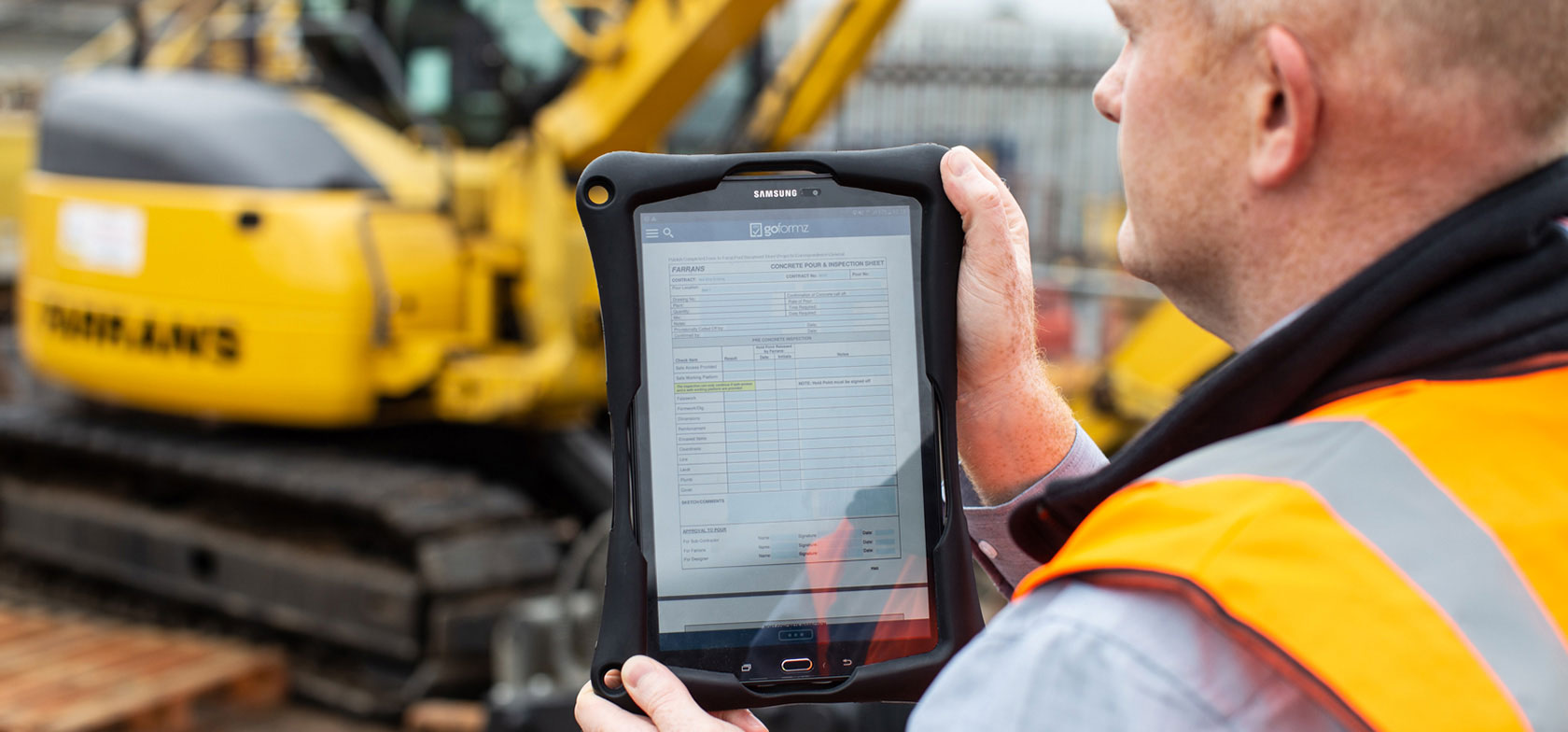 Farrans Construction engineer holding tablet displaying the GoFormz app, while wearing a safety vest