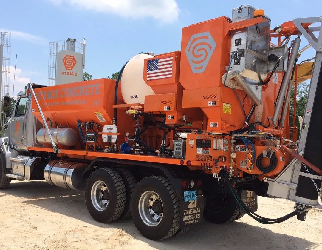 An orange SiteMix truck delivers ready made concrete to a construction site